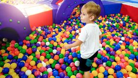 Image of 3 years old toddler boy playing and having fun on the playground with lots of small colorful plastc ball. Child. Photo of 3 years old toddler boy royalty free stock images