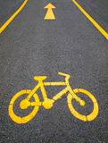 Image with yellow arrows and bicycle. Yellow arrows and bicycle sign path on the road Stock Photography
