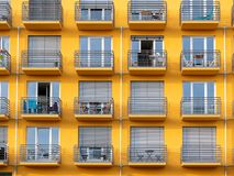 Image of yellow high rise building with windows and balconies and blinds stock photos