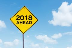 Yellow signpost with text of 2018 ahead. Image of yellow signpost with text of 2018 ahead under blue sky Royalty Free Stock Images