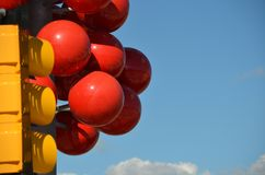Red, yellow, blue, and white abstract in Portland, Oregon. This is an image of a yellow transit signal light, red ball sculpture, blue sky, and white cloud near stock photo