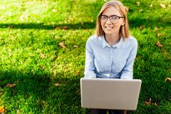Image of a young amazing lady, sitting in a park, using a laptop computer, sits on a green lawn. stock photos