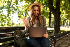 Excited happy woman outdoors sitting using laptop computer. stock photo