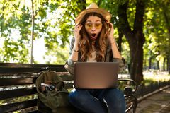 Excited happy woman outdoors sitting using laptop computer. royalty free stock photography