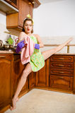 Image of young beautiful super flexible woman pinup girl wiping glass in purple gloves at the kitchen with leg-split Stock Photo