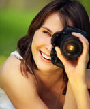 Image of young beautiful woman photographing in summer park Stock Photo