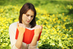 Image of young beautiful woman in summer park reading book Stock Images