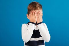 Image of Young boy in sweater covering his face. Over blue background Royalty Free Stock Image