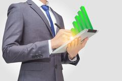 Business man using touchpad, tablet to retrieve and analyze data with green stick graph indicator on the top of tablet PC Royalty Free Stock Photo