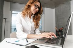Business woman dressed in formal clothes shirt indoors using laptop computer royalty free stock image