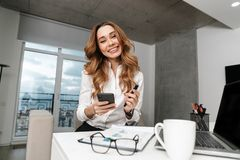 Business woman dressed in formal clothes shirt indoors using mobile phone royalty free stock image