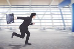 Young businessman running on the airport terminal Royalty Free Stock Image