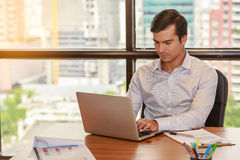 Image of young businessman working with laptop in office Stock Image