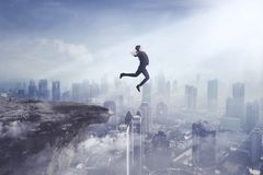 Young businesswoman jumping off a cliff. Image of young businesswoman wearing formal suit while jumping off a cliff to a city stock photos