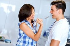 Young couple in the kitchen tasting food royalty free stock image