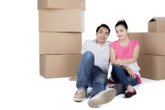 Young couple is relaxing in his new home. Image of young couple is relaxing together during moving to his new home and sitting near stacks of cardboard Royalty Free Stock Images