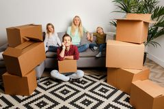 Image of young couple with son and daughter sitting on floor among cardboard boxes stock photography