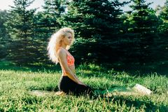 Image of young curly-haired sports woman practicing yoga on rug royalty free stock photography