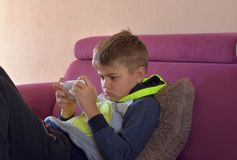 Image of young cute boy playing games on mobile phone lounging on sofa stock photo