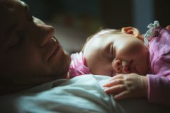 Image of young dad with cute little daughter in. His arms. Father and newborn baby child indoor stock photography