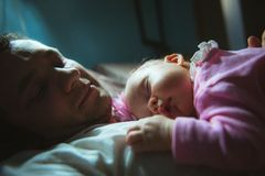 Image of young dad with cute little daughter in. His arms. Father and newborn baby child indoor stock images