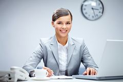 Successful employer. Image of young employer looking at camera while planning work in office Royalty Free Stock Photography