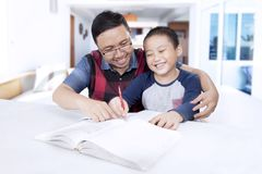 Little boy doing homework with his father Royalty Free Stock Photos