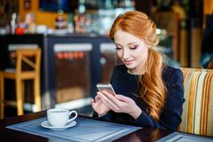 Image of young female reading sms on the phone in cafe. Stock Photos