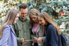 Image of young friends outdoors with a computer in hands of a young man. They look at the tablet. Close-up Stock Photos