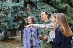Image of young friends outdoors with a computer in hands of a young man. Royalty Free Stock Images