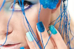 The image of a young girl with blue makeup and manicure. Stock Images