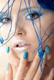 The image of a young girl with blue makeup and manicure. Royalty Free Stock Images