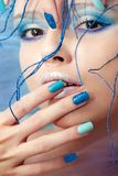 The image of a young girl with blue makeup and manicure. Stock Image