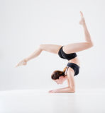 Image of young girl doing acrobatic stunt. On white Stock Images