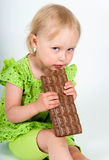 Young girl eating bar of chocolate Royalty Free Stock Images
