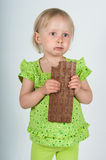 Young girl eating bar of chocolate Royalty Free Stock Photography