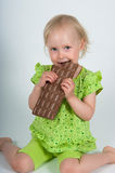 Young girl eating bar of chocolate Stock Photos