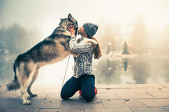Image of young girl with her dog, alaskan malamute, outdoor Royalty Free Stock Photography