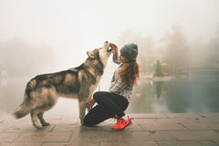 Image of young girl with her dog, alaskan malamute, outdoor. At autumn or winter. Dog food. Feeding domestic pet. Husky Royalty Free Stock Image