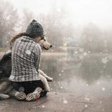 Image of young girl hug her dog, alaskan malamute, outdoor stock photo
