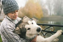 Image of young girl hug her dog, alaskan malamute, outdoor stock photography