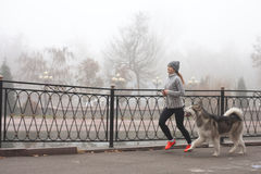 Image of young girl running with her dog, alaskan malamute royalty free stock image
