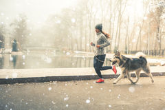 Image of young girl running with her dog, alaskan malamute stock photo