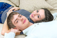 Young guy and a girl lying on the couch Royalty Free Stock Image