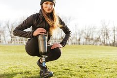 Image of young handicapped sportswoman in tracksuit, squatting a. Image of young handicapped sportswoman in tracksuit squatting and touching bionic leg outside royalty free stock images