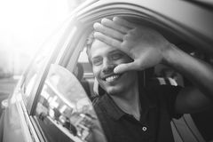 Say hello. Close up side portrait of happy caucasian man driving car. Image of young handsome guy sitting in car and meet someone Royalty Free Stock Images
