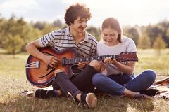 Image of young handsome man with dark curly hair teaches playing guitar her friend, couple have picnic in meadow, have romantic, stock photography