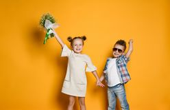 Image of young happy caucasian boy gives a flowers to his girlfriend isolated over yellow background. royalty free stock photo