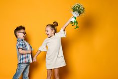 Image of young happy caucasian boy gives a flowers to his girlfriend isolated over yellow background. Little girl is happy to receive a bouquet of daisies from royalty free stock photography
