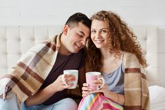 Image of young happy couple drinking coffee or tea in bed in morning, sitting under warm plaid, enjoing weekend, woman looks at stock photo